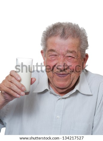 Senior holds happy a glass of milk in hand - stock photo