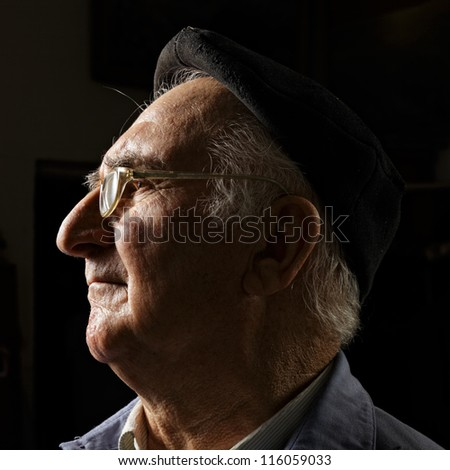 Senior in cap and eyeglasses sideview head and shoulders portrait - stock photo
