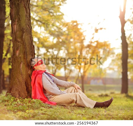 Senior in superhero outfit leaning on tree in park shot with tilt and shift lens - stock photo