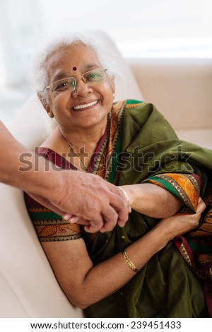 Senior Indian woman holding a hand of her husband and looking at the camera - stock photo