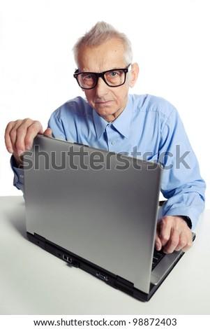 Senior is working on laptop. - stock photo