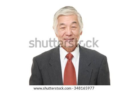 senior Japanese businessman smiles - stock photo