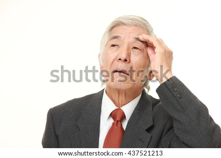 senior Japanese businessman wearing a gray suit has lost his memory - stock photo