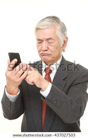 senior Japanese businessman wearing a gray suit  using smart phone looking confused - stock photo