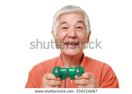 senior Japanese man enjoying a video game - stock photo