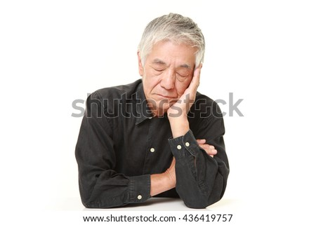 senior Japanese man  in a black shirts sleeping on the table - stock photo