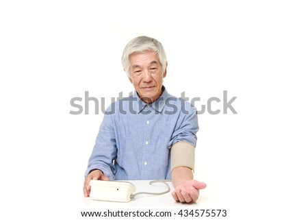 senior Japanese man in a blue shirts checking his blood pressure - stock photo