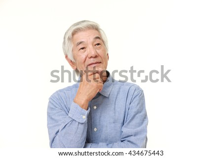 senior Japanese man in a blue shirts thinks about something  - stock photo