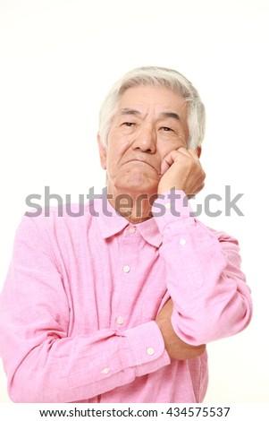 senior Japanese man in a pink shirts worries about something - stock photo
