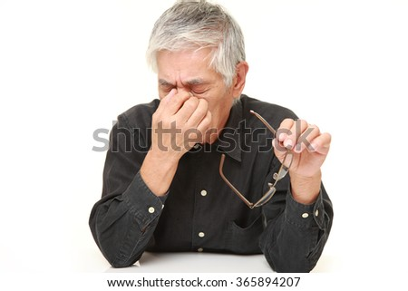 senior Japanese man suffers from Asthenopia - stock photo
