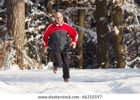 senior jogging in the snow - stock photo