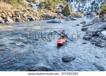 senior kayaker in a whitewater kayak paddling upstream of Arkansas River above Hecla Junction, Colorado in winter scenery - stock photo