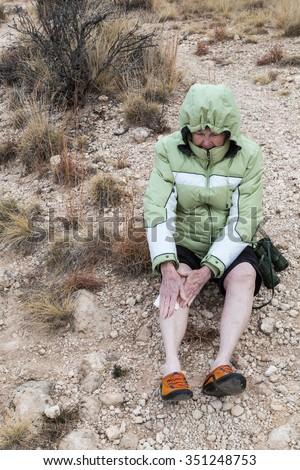 Senior lady bundled against cold weather holding bandage on her bleeding leg after falling in loose rocks. - stock photo