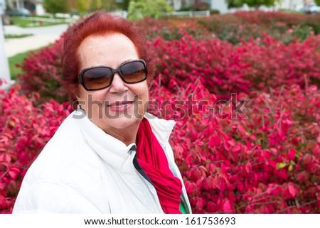 Senior lady enjoying the autumn around burning bushes - stock photo