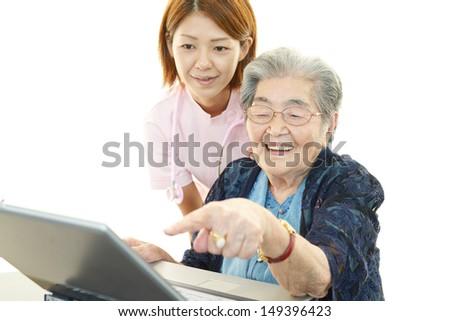 Senior lady enjoys computer - stock photo