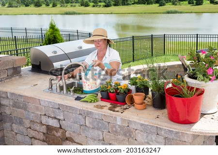 Senior lady filling a watering can at a sink in a summer kitchen on an outdoor patio to water her collection of potted plants and houseplants standing ready on the counter with a lake backdrop - stock photo
