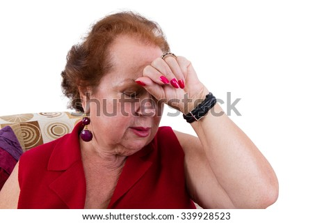 Senior lady having a bad day suffering from a headache holding her hand to her forehead as she closes her eyes against the pain, closeup view seated in an armchair isolated on white - stock photo