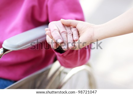 Senior Lady in Wheelchair Holding Hands with Caretaker - stock photo