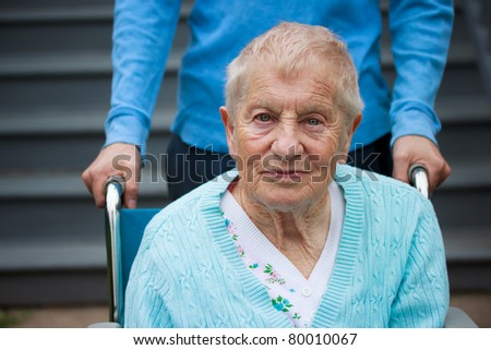 Senior lady in wheelchair with caretaker - stock photo