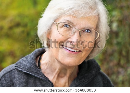 Senior lady looking relaxed and happy in font of nature background - stock photo