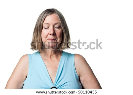 Senior lady looking to the ground, obviously upset and thoughtful - stock photo