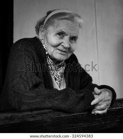 Senior lady on the porch, black and white - stock photo