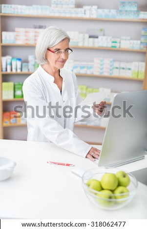 Senior lady pharmacist wearing glasses and a white lab coat working in a pharmacy checking a prescription on the computer - stock photo