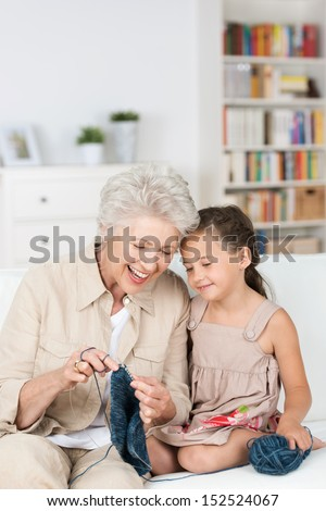 Senior lady teaching her granddaughter to knit as they relax together on the the sofa laughing together with enjoyment - stock photo