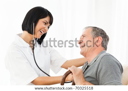 Senior laughing with his nurse at home - stock photo