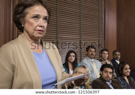 Senior lawyer standing with paper in courtroom and people in the background - stock photo