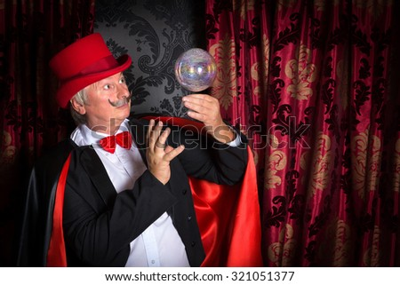 Senior magician performing on stage with a crystal ball - stock photo