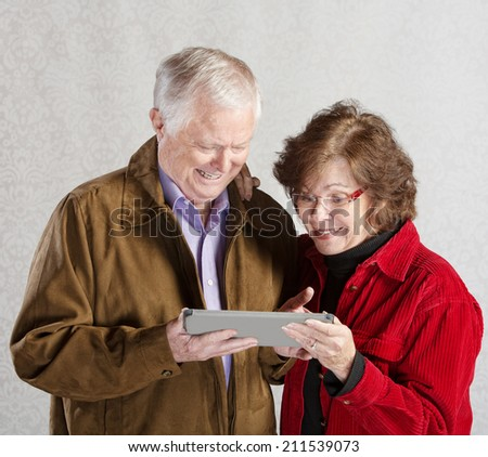 Senior male and female excited with computer tablet - stock photo