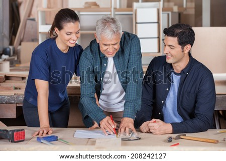 Senior male carpenter drawing blueprint with team at table in workshop - stock photo