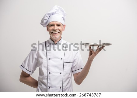 Senior male chief cook in uniform holding tray a  on grey background. - stock photo
