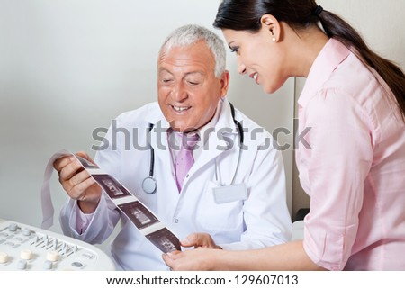 Senior male doctor and female patient looking at ultrasound print - stock photo