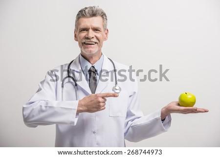 Senior male doctor holding green apple on grey background. - stock photo