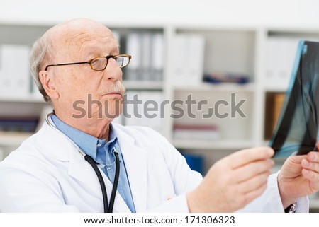 Senior male doctor or radiologist wearing glasses dressed in a lab coat and stethoscope checking an x-ray film with a serious expression - stock photo