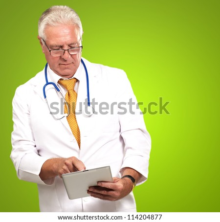 Senior Male Doctor Using Digital Tablet On Green Background - stock photo