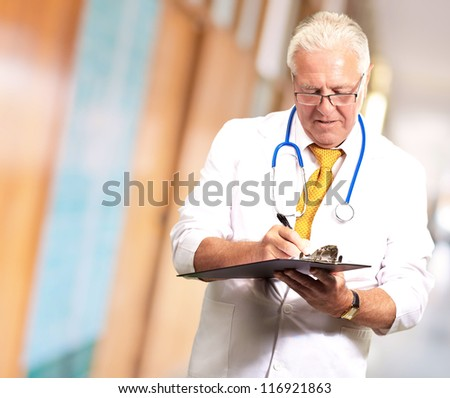 Senior Male Doctor Writing On Clipboard, Indoor - stock photo