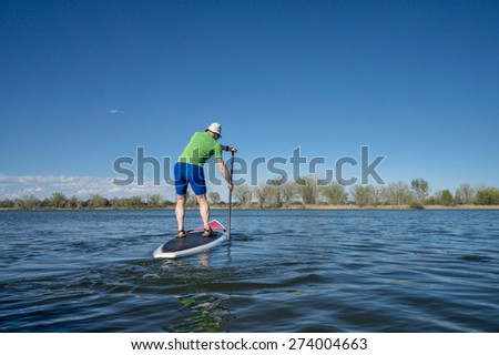 Senior male exercising on stand up paddling (SUP) board.. Early spring on calm lake in Fort Collins, Colorado.. - stock photo