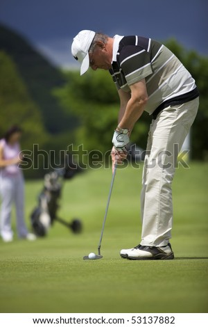 Senior male golf player putting a golf ball on the green into the hole with female golf player waiting in the background. - stock photo