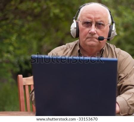 senior male on laptop, place advert on laptop - stock photo