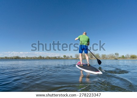 senior male on SUP (stand up paddleboard) on a lake under Colorado blue sky - stock photo