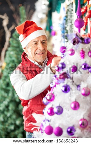 Senior male owner in Santa hat decorating Christmas tree with balls at store - stock photo