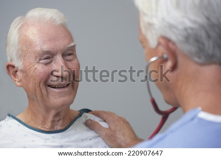 Senior male patient being examined by doctor - stock photo