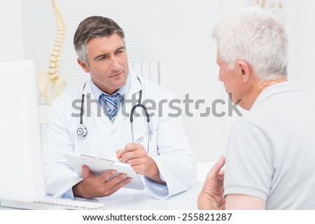 Senior male patient sharing problems with doctor in clinic - stock photo