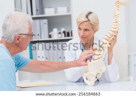 Senior male patient showing spine problems to female doctor at table in clinic - stock photo
