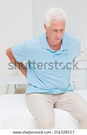 Senior male patient suffering from backache in clinic - stock photo