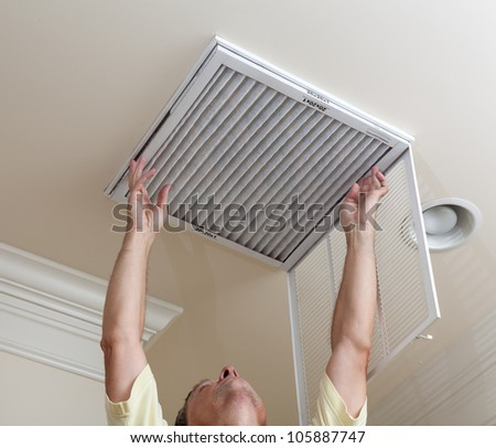 Senior male reaching up to open filter holder for air conditioning filter in ceiling - stock photo