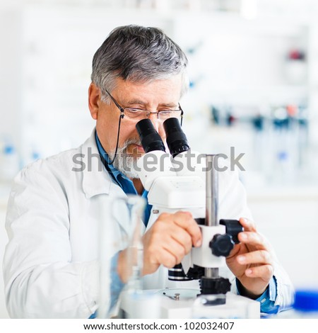 senior male researcher carrying out scientific research in a lab using a microscope (shallow DOF; color toned image) - stock photo
